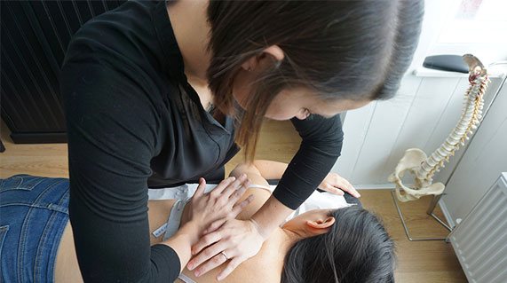 Osteopath in Haywards Heath using hands to treat a patients back